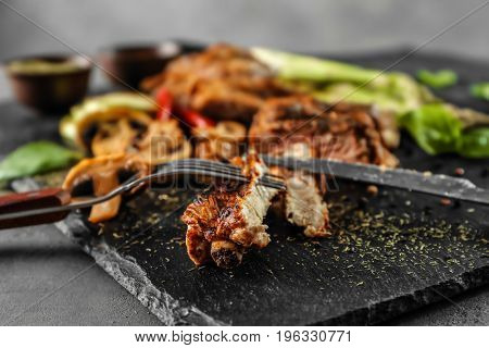 Cutting of delicious grilled spare ribs on black slate plate