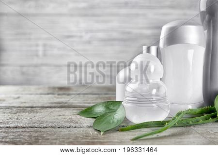 Different deodorants and leaves on wooden background