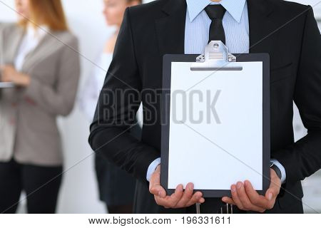 Unknown businessman holds clipboard with copy space area.