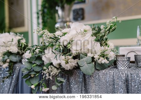 White floral decoration with greenery on the table for the wedding ceremony