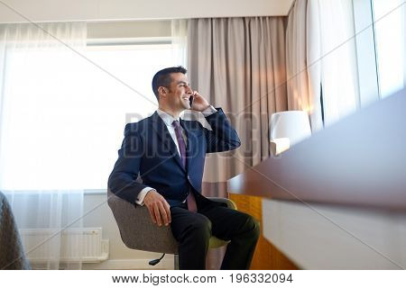 business trip, people and communication concept - businessman calling on smartphone at hotel room