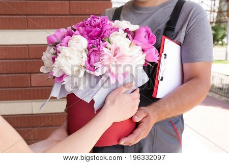 Young woman receiving beautiful peony flowers from delivery man