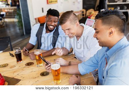 people, male friendship and technology concept - happy friends with smartphone drinking beer at bar or pub
