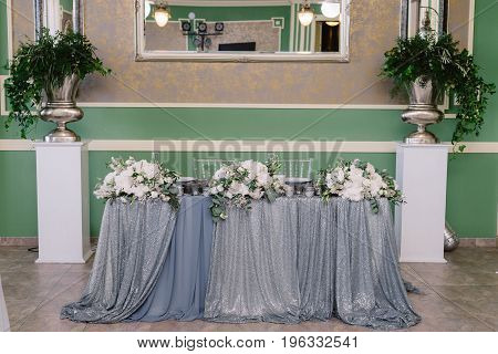 Wedding table decoration in white and silver colors for the fiance and fiancee in the restaurant