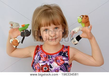 child, kid,(little girl) playing with dolls is wearing on the fingers.