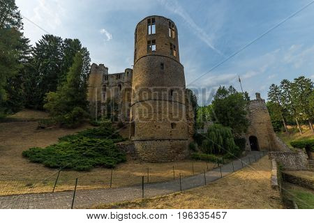 Medieval castle among trees and blue sky in Luxembourg.