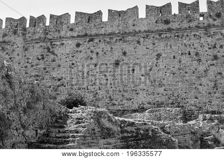 big ancient wall of old stone fortress for a background monochrome tone