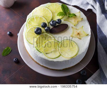 Lemon yogurt mousse cake, mojito berry cake on a plate on a brown stone background