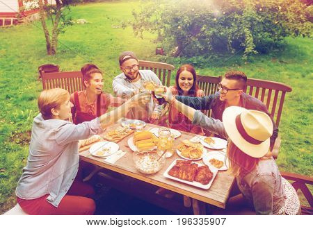 leisure, holidays, eating, people and food concept - happy friends clinking glasses and celebrating at summer garden party