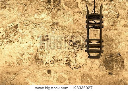 one steel lamp on an ancient stone wall of color sepia
