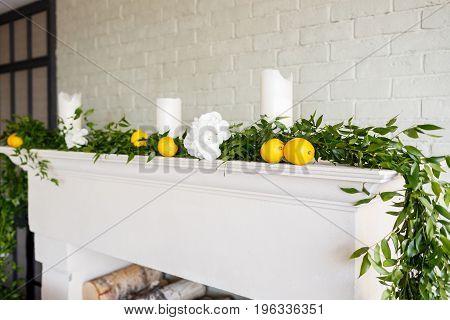 white fireplace decorated with greenery and lemons. Lemons on background. Style lemon. Wedding decor