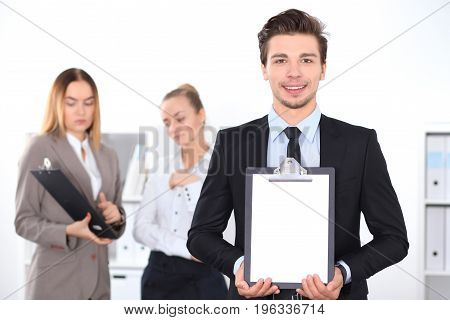 Cheerful business man in office with colleagues in the background, sturt  up team