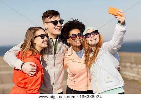 people, friendship and technology concept - group of smiling teenage friends taking selfie with smartphone outdoors