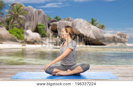 fitness, sport and healthy lifestyle concept - woman doing yoga in twist pose on mat over exotic tropical beach background