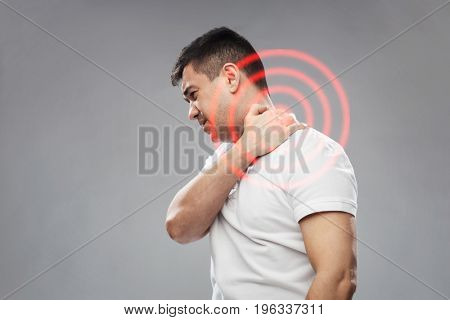 people, healthcare and problem concept - unhappy man suffering from neck pain over gray background