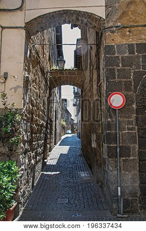 Orvieto, Italy - May 17, 2013. Overview of an alley with old buildings and scooter under a sunny blue sky, at the town of Orvieto, a pleasant and well preserved medieval city. Located in Umbria