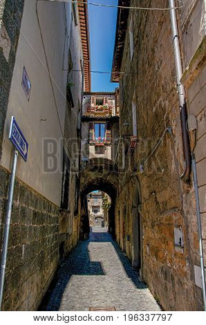 Overview of a narrow alleyway with old buildings and traffic sign at the town of Orvieto, a pleasant and well preserved medieval city. Located in Umbria, central Italy