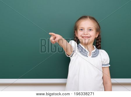 Pupil posing at school board, empty space, education concept