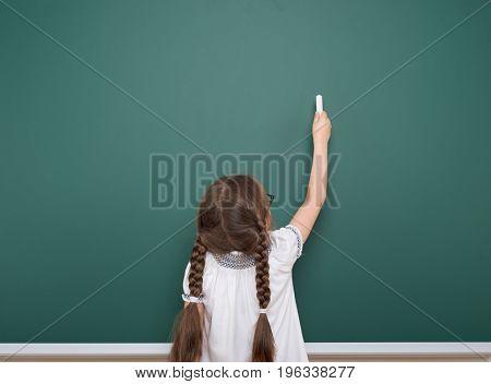 Schoolgirl writing chalk on a blackboard, empty space, education concept