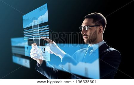 business, augmented reality and future technology concept - businessman in glasses working with transparent tablet pc computer and virtual exchange charts projections over black background