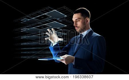 business, people and future technology concept - businessman in suit working with transparent tablet pc computer and virtual construction hologram over black background