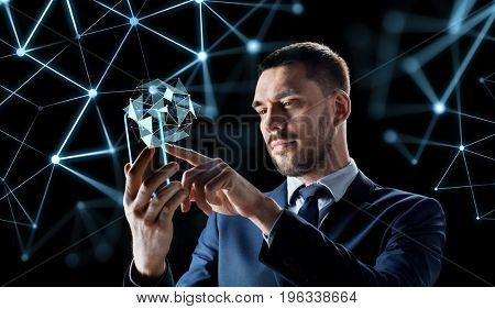 business, augmented reality and future technology concept - businessman working with transparent smartphone and virtual low poly shape projection over black background