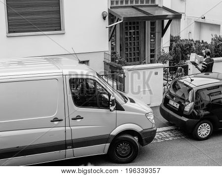 PARIS FRANCE - JUL 12 2017: Black and white Aerial view of delivery man with cardboard parcel box writing info notice to absent client to come back later to the the consignee to deliver the cardboard parcel