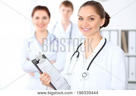 Happy female doctor keeping medical clipboard while medical staff are at the background. Successful team at health care and medicine concept