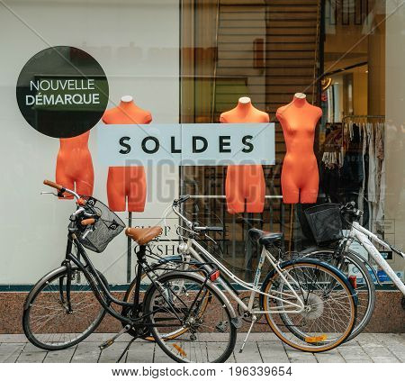 STRASBOURG FRANCE - JUL 21 2017: Female bicycles parked in front of the Sales Soldes sign with naked mannequins in the fashion store showcase glass