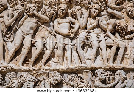 Close-up of the opulent and elaborated embossed sculptures in the Orvieto Cathedral (Duomo) on a sunny day in Orvieto, a pleasant and well preserved medieval town. Located in Umbria, central Italy