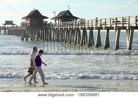 MIAMI, FLORIDA - NOVEMBER 28, 2013: Happy senior couple enjoys a romantic stroll on the beach near the pier