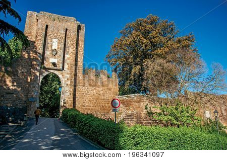 Overview of stone wall and gateway, green hills, trees and a blue sunny sky. In town of Orvieto, an ancient, pleasant and well preserved medieval town. Located in Umbria, central Italy.