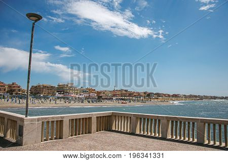 Overview in the foreground of marble pier, with the beach and the city of Ostia in the background, on a sunny day. The town is a seaside resort and ancient port of Rome. Located in the Lazio region