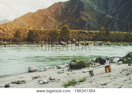 View of self-made wooden bench standing alone on sandy and rocky beach of fast Katun river; mountains hills and sparse trees in defocused background Altai Kuyus district Russia