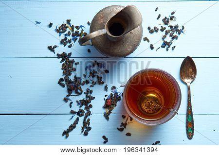 Top Aerial View On Desk With Glass Of Tea, Jug, Tea Leaves And Teaspoon