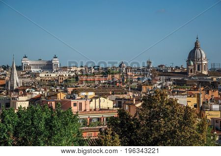 Overview of trees, cathedrals domes and roofs of buildings in the sunset of Rome, the incredible city of the Ancient Era, known as