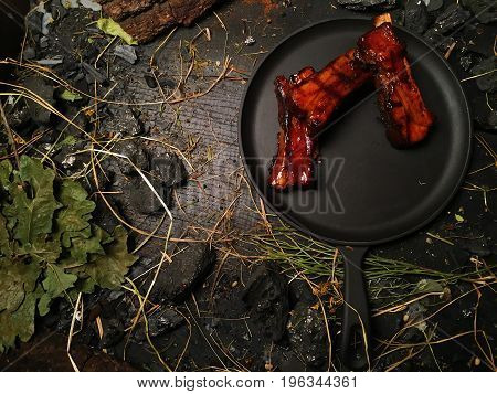 Appetizing ribs lie in a frying pan. Fried oil ribs lie on a black frying pan. The frying pan stands on a dark wooden table among pieces of coal. Hay is lying around the frying pan.