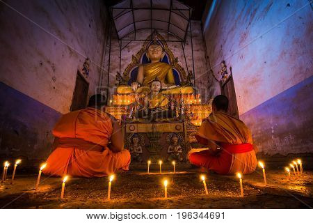 Novice Monk meditating fire candles to the Buddha in thailand