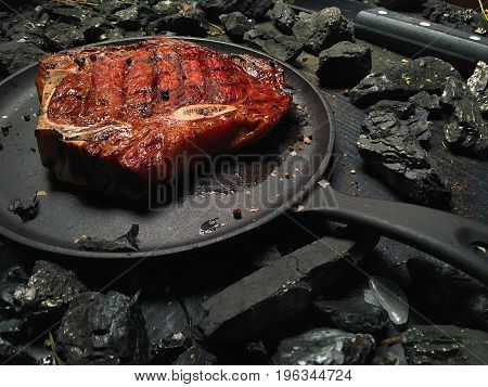 Juicy steak lies in the oil in the frying pan. A large roasted steak lies on a dark frying pan. The frying pan stands on a dark wooden table among pieces of coal.