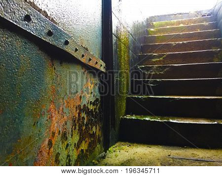 Rusty steel door with moldy stairs leading up to daylight