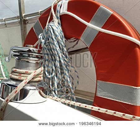 Nautical image of Boat Gear on the deck of a yacht including a two speed deck winch lifebuoy and bundle of rope closeup.