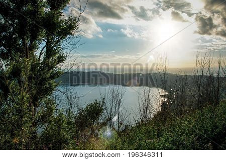 View of the slopes, forests and hills of Lake Albano in a cloudy sunset. Albano is a quiet and bucolic countryside region near Rome. Located in the Lazio region, central Italy. Retouched photo