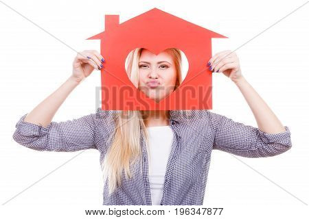 Ownership and property concept. Happy woman holding red paper house with hole in heart shape loving new home.