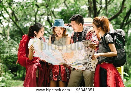 Group of backpacker friend checking a map for direction during travel trip in forest. Friendship adventure concept.