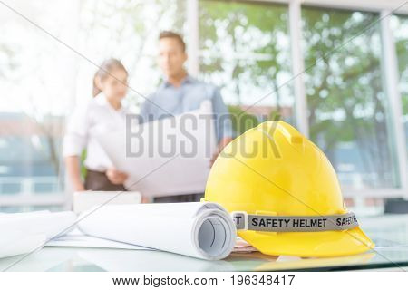 Close up shot of safety helmet and blueprint on workplace with engineer and architect discussing about new construction project in background