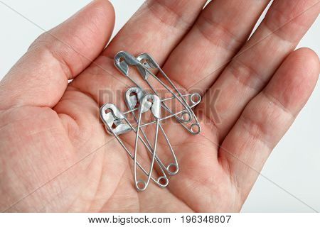 Hand holding sewing safety pins close up.