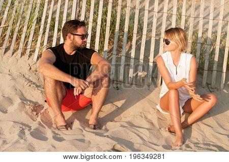 Young Beautiful Couple Sitting On Beach Enjoy Sunset And Romantic Atmosphere.