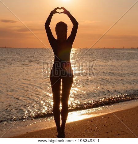 Silhouette Of A Young Woman Practicing Yoga At The Seaside At Sunset