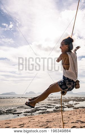 Vertical picture of a girl raising her arm while play at the swing on a cloudy day a Las Cabanas Beach Philippines.