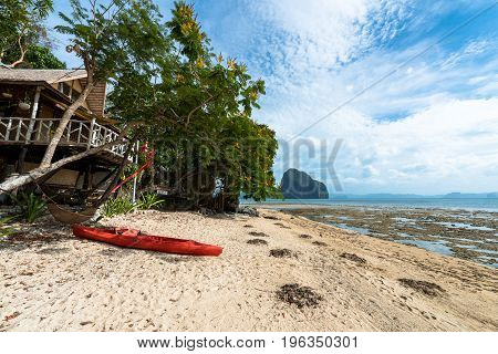 Beachfront house with kayak and a hammock at Las Cabanas Beach located in El Nido's Island Philippines. Tropical weather and vegetation.